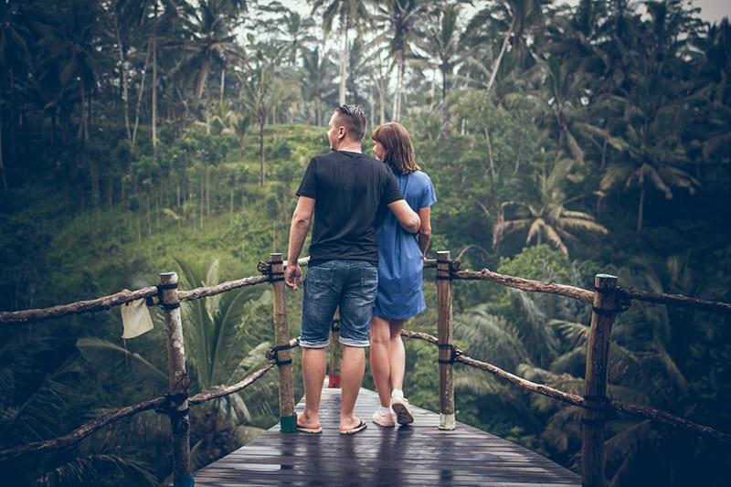 Ein Paar stand auf einer hängenden Brücke und schaute in den Wald