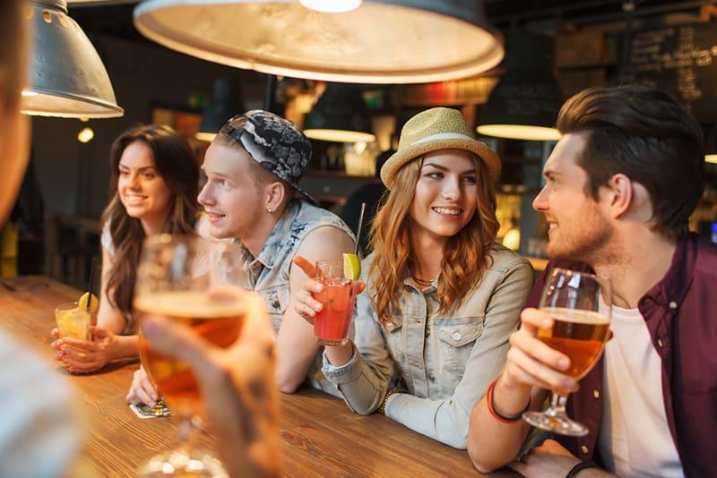 Ein Paar schaut sich an, während es mit Freunden in der Kneipe sitzt und Bier trinkt