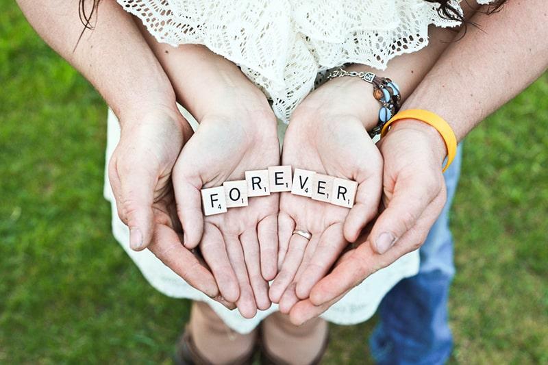 """ein Paar, das """"Forever"""" -Scrabble-Buchstaben auf den Handflächen hält"""