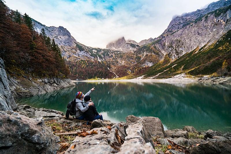 ein Paar sitzt auf der Klippe in der Nähe des Sees