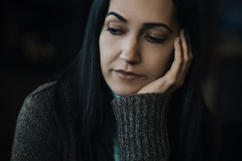 ein Porträt einer traurigen Frau, die im Dunkeln sitzt