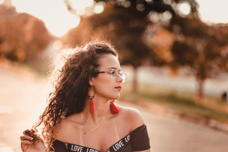ein Porträt eines Mädchens mit krausem Haar mit Brille und roten Ohrringen