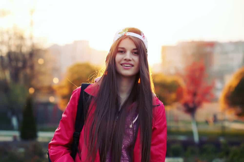 ein Porträt eines glücklichen Mädchens mit braunen Haaren und einer Kappe auf dem Kopf