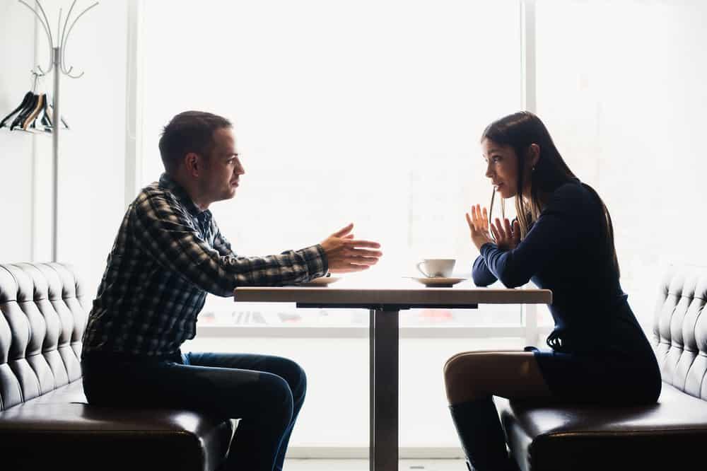 ein Streit zwischen einer attraktiven Geschäftsfrau und ihrem Mann in einem Café