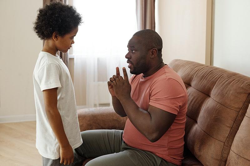 Ein Vater spricht mit seinem Sohn, während er mit den Händen gestikuliert