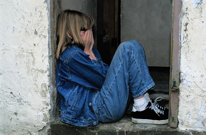 Ein einsames Kind bedeckt ihr Gesicht mit Handflächen, während es auf der Tür der Ruinen sitzt