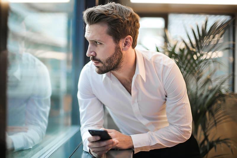 Ein ernster Mann hält sein Smartphone und schaut durch das Fenster