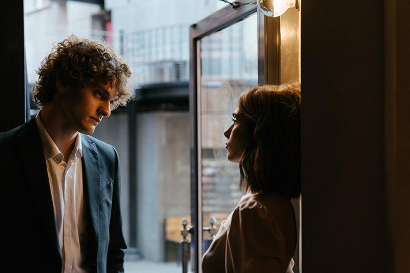 Ein ernster Mann und eine Frau sehen sich an, während sie in der Nähe der Tür stehen
