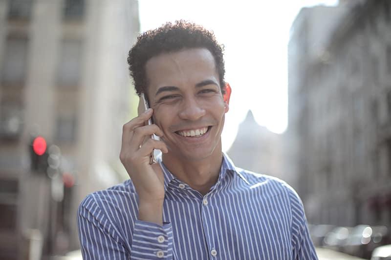 Ein fröhlicher Mann, der auf einem Smartphone spricht, während er auf der Straße geht