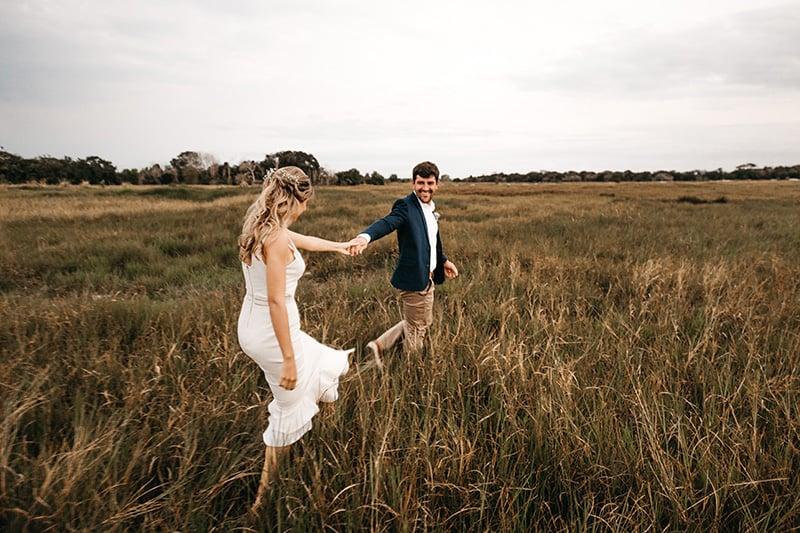 ein frisch verheiratetes Paar, das Hände hält, während es auf der Wiese geht