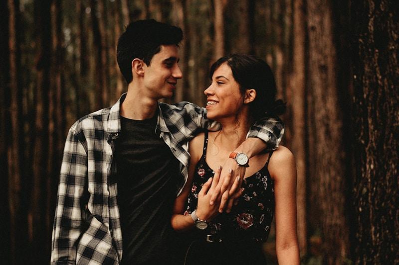 ein glückliches Paar, das sich im Wald ansieht