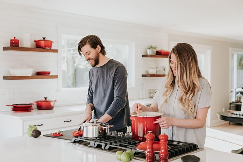 ein glückliches Paar, das gemeinsam in der Küche Essen zubereitet