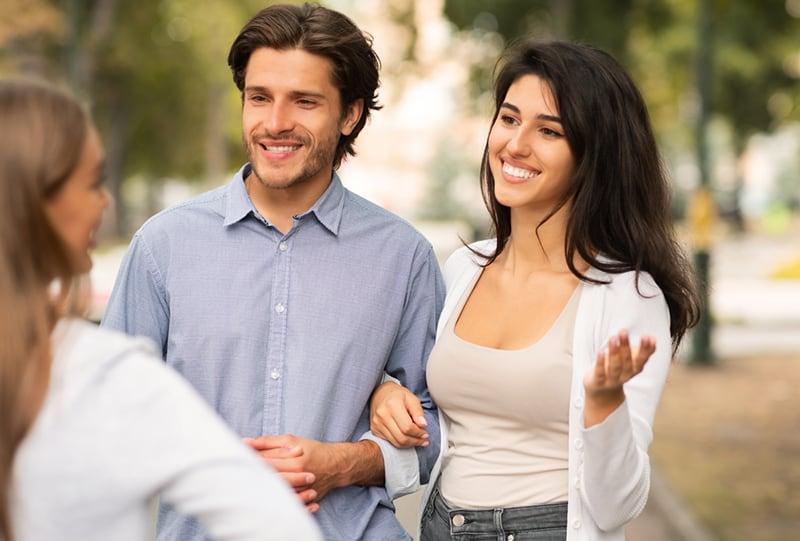 ein glückliches Paar, das mit einer Freundin spricht, während es auf dem Bürgersteig steht