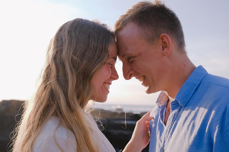 ein glückliches Paar lächelt während sie sich berühren, während ihre Stirn in der Natur steht