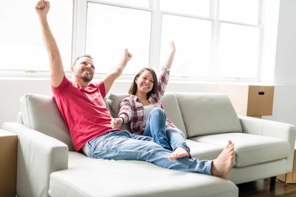 ein glückliches Paar sitzt auf einer Couch in einer neuen Wohnung