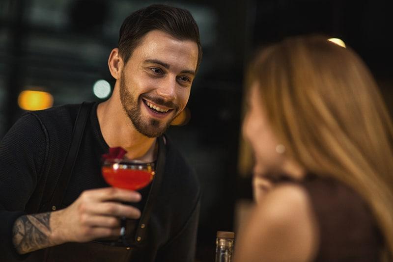 Ein hübscher Barkeeper lächelt, während er einer allein sitzenden Frau einen roten Cocktail anbietet