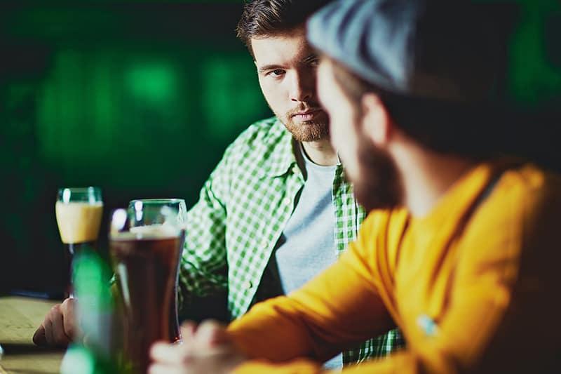 Ein introvertierter Mann, der seinen Freund ansieht, während er an der Bar sitzt