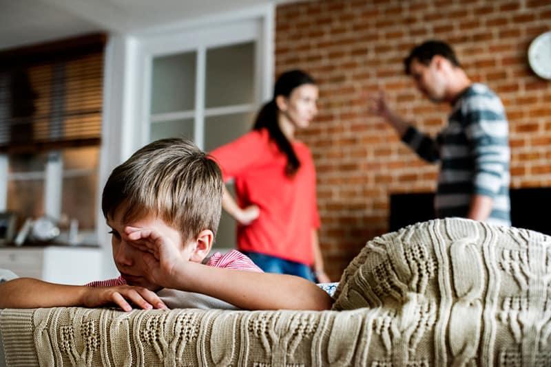 Ein kleiner Junge weint, während seine Eltern sich hinter ihm streiten