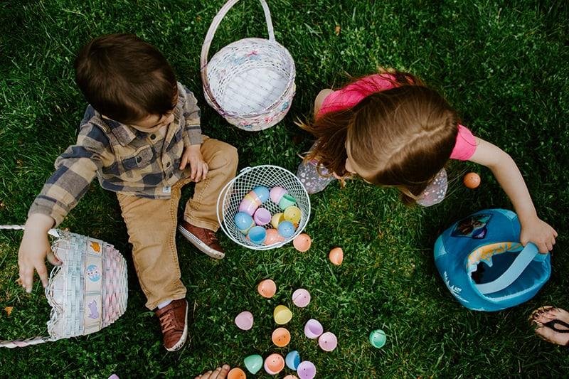 ein kleines Mädchen und ein Junge, die mit Plastikbällen spielen, während sie auf dem Gras sitzen