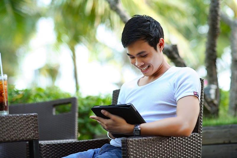 ein lächelnder Mann, der eine Tablette betrachtet, während er im Café sitzt