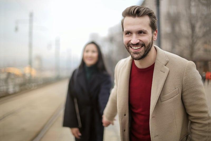 Ein lächelnder Mann hält die Hand seiner Freundin und geht auf dem Bürgersteig vor ihr her