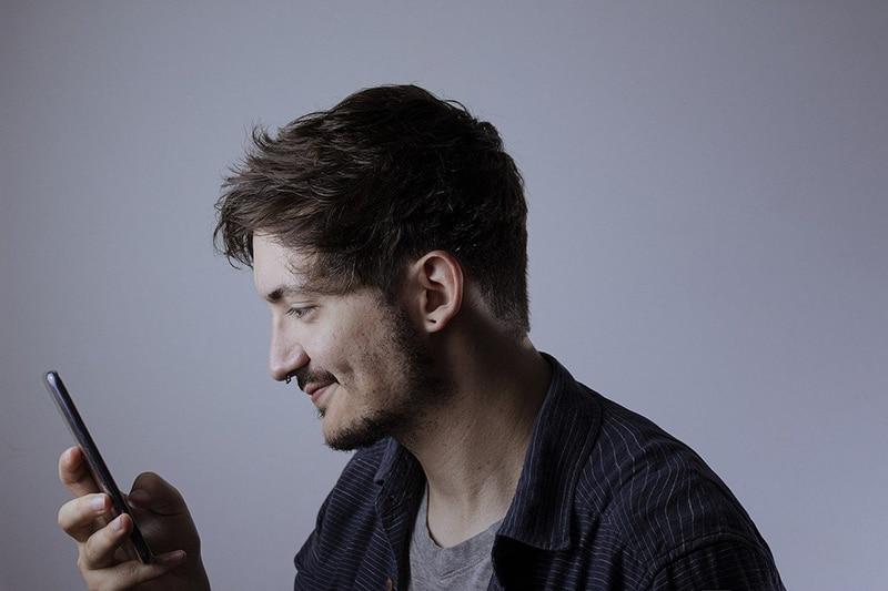 ein lächelnder Mann, der ein Smartphone hält und es benutzt