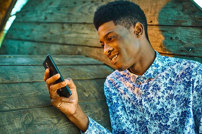 ein lächelnder Mann, der ein Smartphone hält, während er sich an die Holzwand lehnt