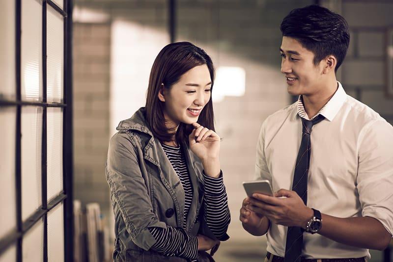 Ein lächelnder Mann, der in der Nähe einer lächelnden Frau steht und ihr etwas auf seinem Smartphone zeigt