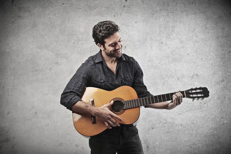 Ein lächelnder Mann mit schwarzen Haaren spielt Gitarre, während er in der Nähe der Wand steht
