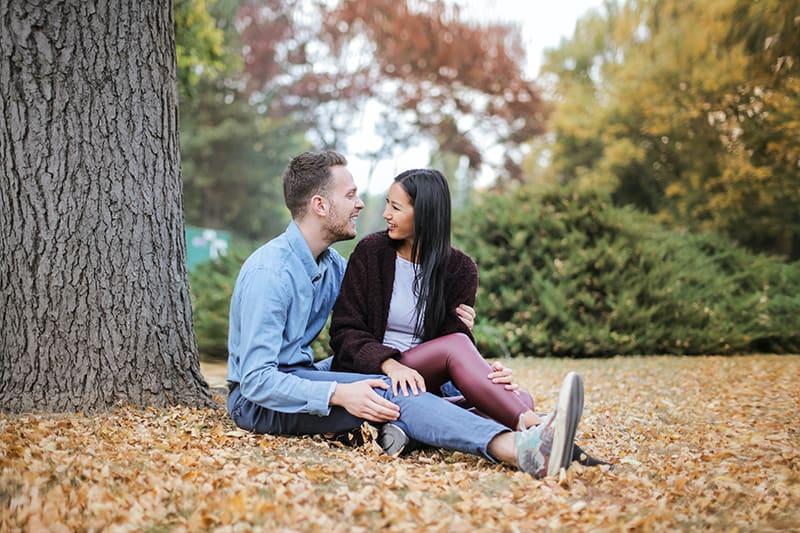 Ein lächelnder Mann und eine lächelnde Frau schauen sich an, während sie auf dem Boden im Park sitzen