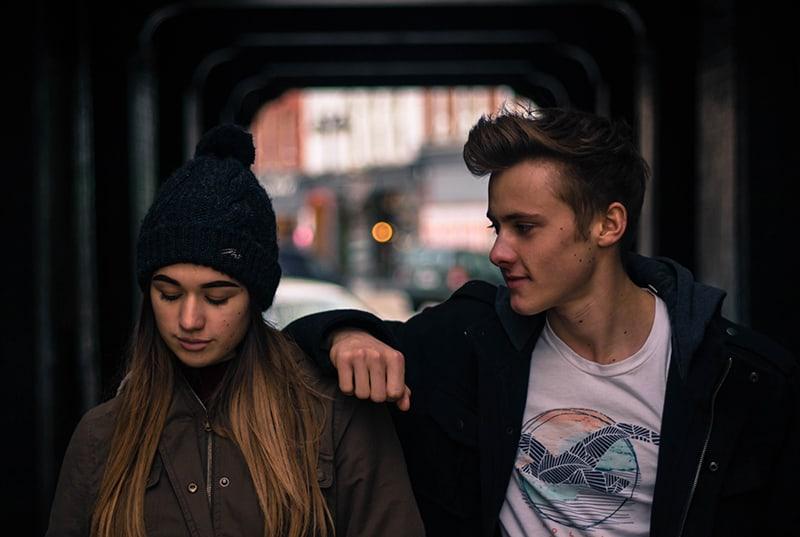 ein lächelnder junger Mann, der sich auf die Schulter einer jungen Frau stützt, während sie nach unten schaut
