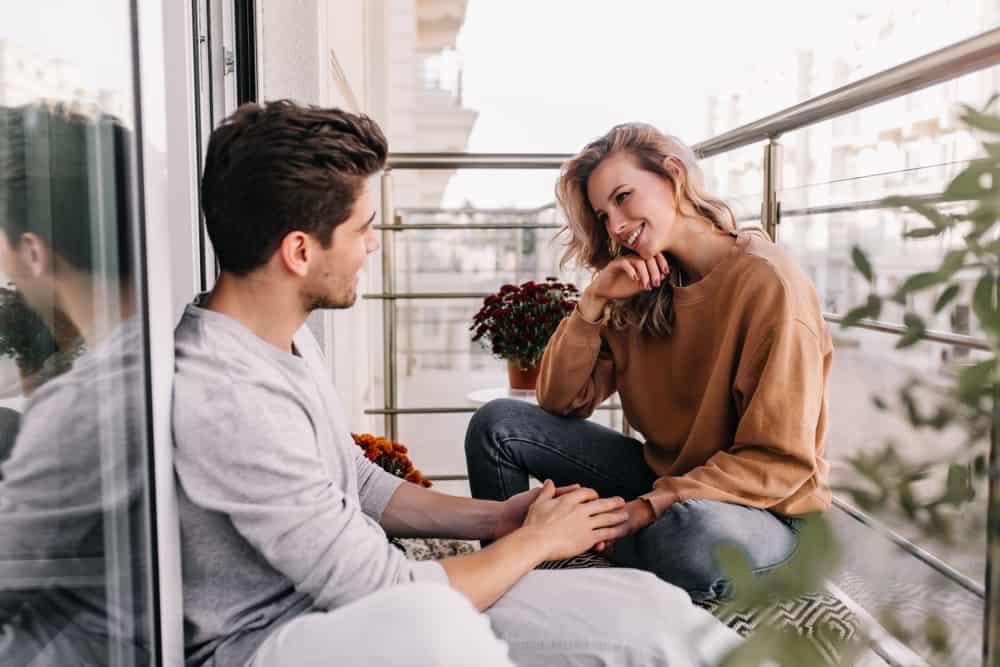 ein lächelndes Liebespaar, das auf dem Balkon sitzt und spricht
