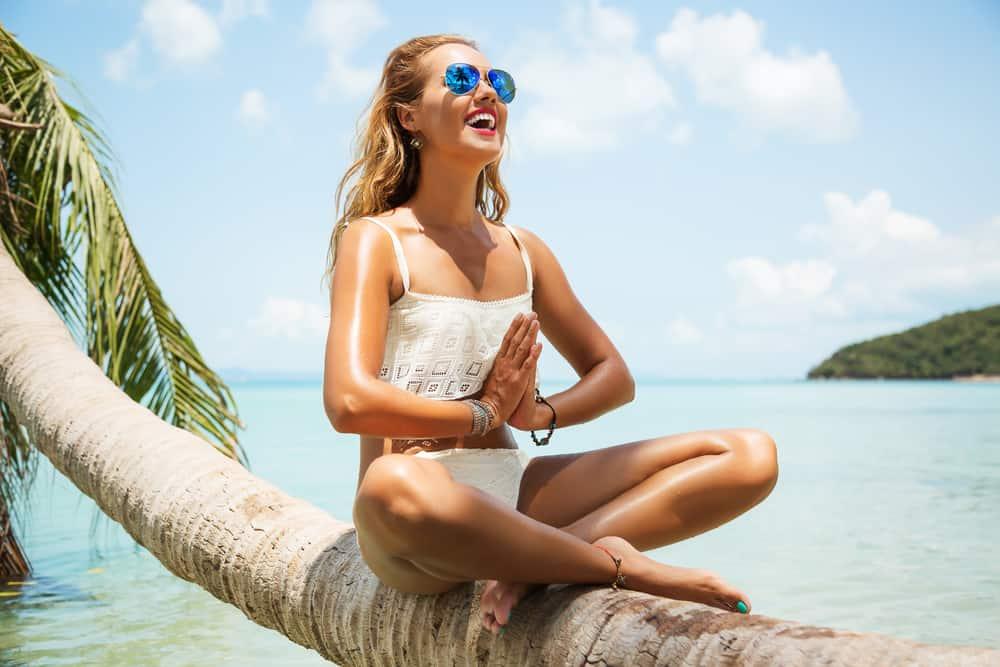 ein lächelndes Mädchen in einem Bikini am Strand auf einer Palme meditiert
