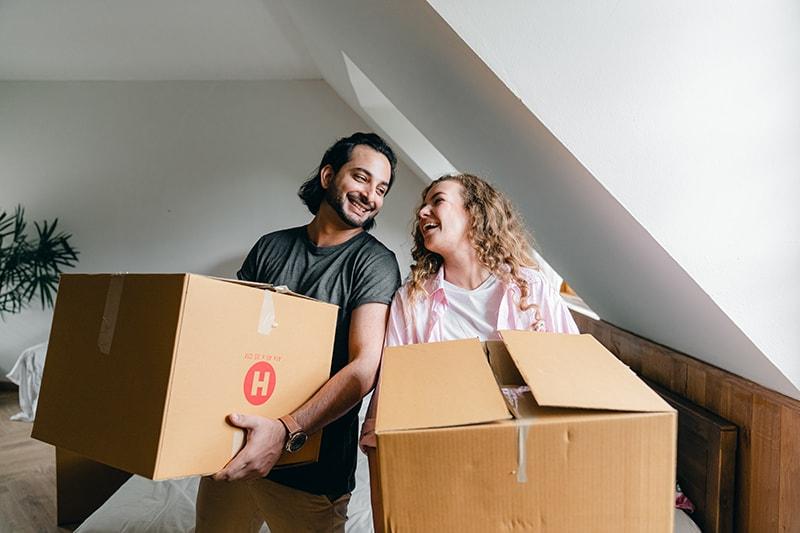 ein lächelndes Paar, das sich ansieht während Sie Kartons in der Wohnung halten