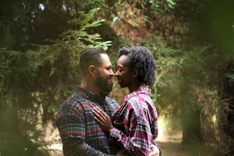 ein lächelndes Paar, das sich gerade küssen will, während es sich unter den Bäumen umarmt