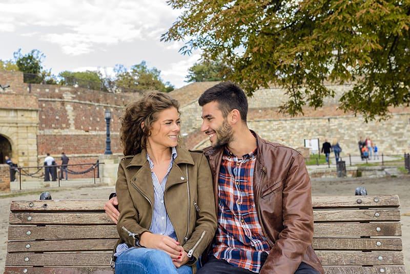 ein lächelndes Paar, das auf der Bank im Park sitzt und sich ansieht