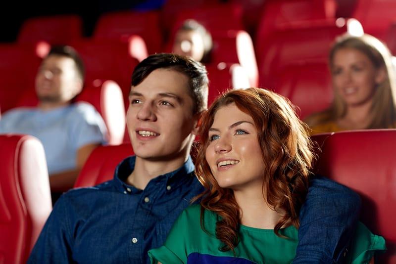 ein lächelndes Paar, das am Theater sitzt, während Mann eine Frau umarmt