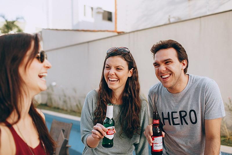 ein lachendes Paar, das Bier hält, während es mit seinem Freund hängt