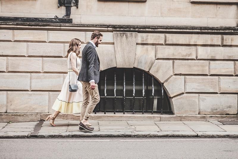 ein liebendes Paar, das Hände hält, während es auf dem Bürgersteig geht