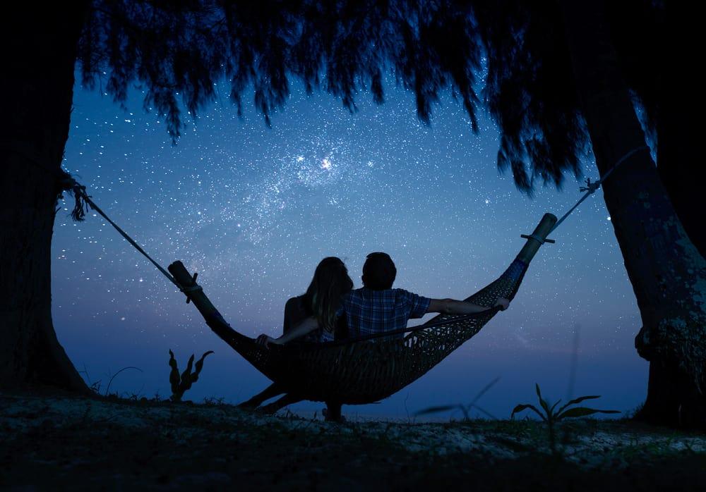 ein liebendes Paar, das in einer Schaukel zwischen zwei Bäumen sitzt und die Sterne beobachtet