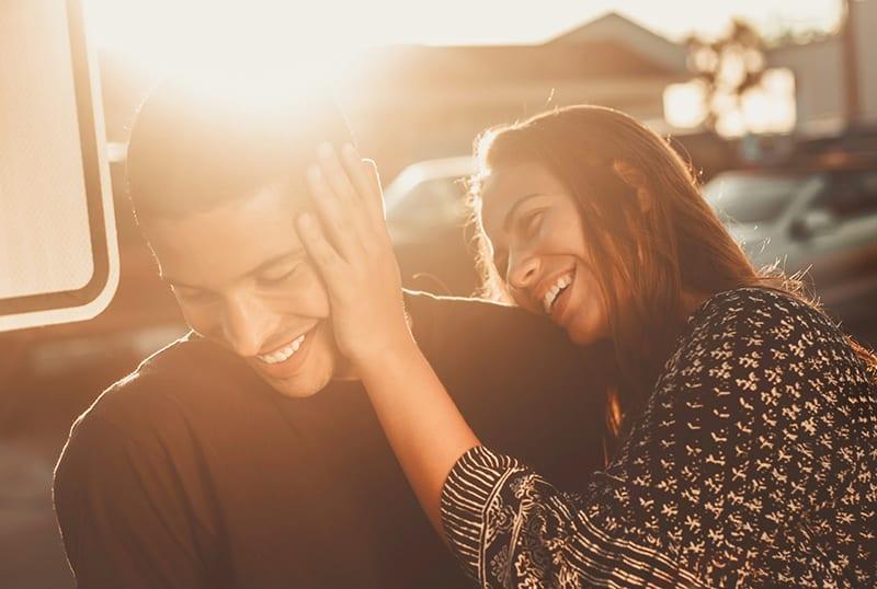 ein liebendes Paar, das zusammen lacht, während es draußen bei Sonnenuntergang sitzt