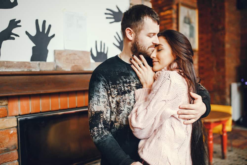 ein liebendes Paar in einer Umarmung, das im Haus steht
