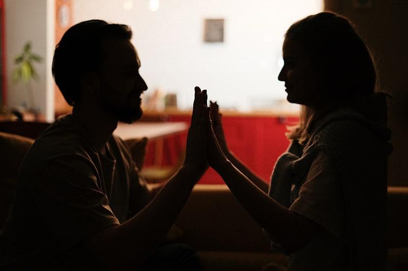 ein liebevolles Paar, das sich im Dunkeln ansieht und ihre Handflächen zusammenfügt
