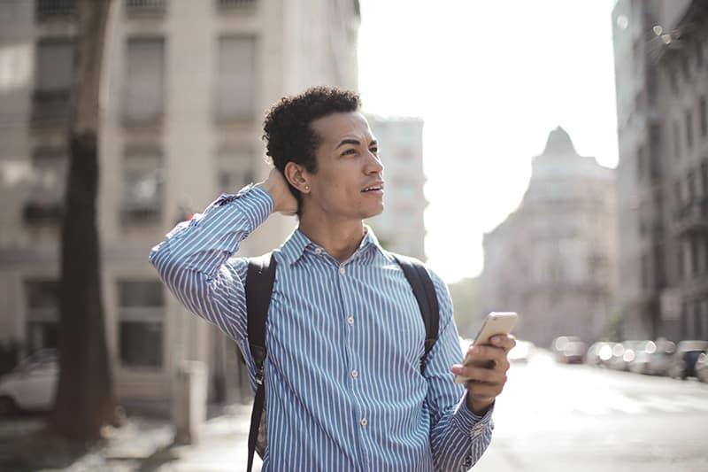 ein nachdenklicher Mann, der ein Smartphone hält und den Kopf berührt, während er auf der Straße steht