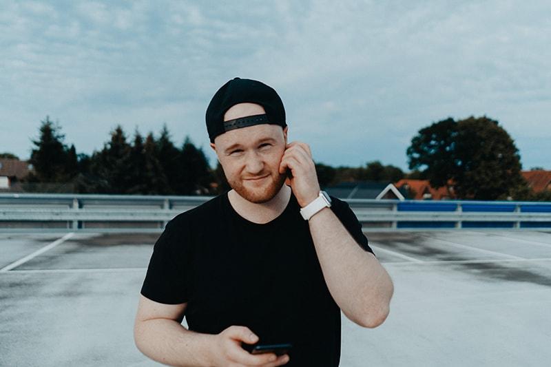 ein nachdenklicher Mann, der ein Smartphone hält, während er auf dem Parkplatz steht