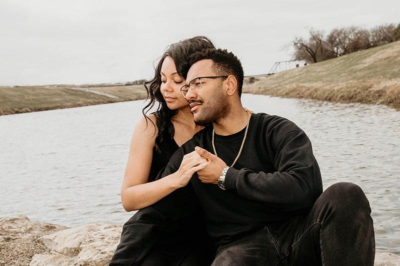 ein Paar, das Hände hält, während es auf dem Felsen in der Nähe des Gewässers sitzt