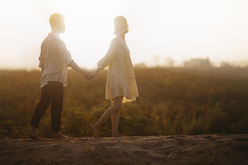 ein Paar Händchenhalten beim Stehen auf dem Sandfeld während des Sonnenuntergangs