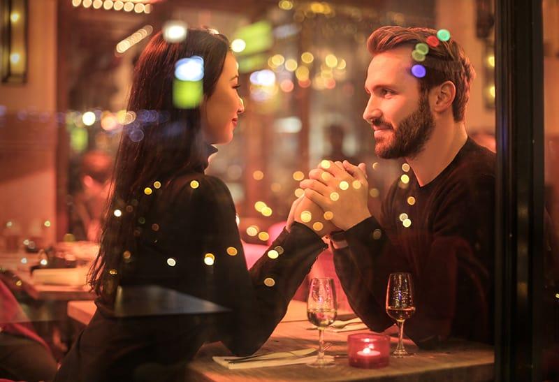 Ein Paar, das sich an den Händen hält und sich im Restaurant ansieht