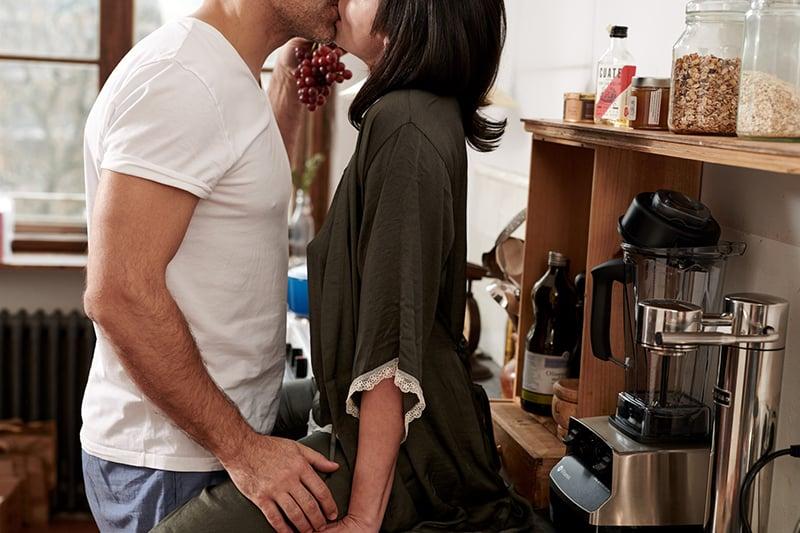 ein paar küssen sich in der küche zu hause
