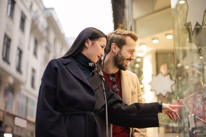 ein Paar, das vor dem Schaufenster steht und in den Laden schaut